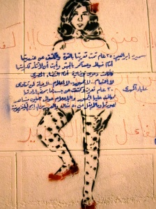 In this piece, a stencil of part of Aliaa's body is presented, with a political message neatly covering the genitalia. Note how the artist uses red highlights, mimicking the way Aliaa herself produced black-and-white images with only red items in color.